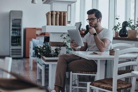 Photo pour Homme d'affaires sérieux utilisant tablette numérique tout en étant assis sur la chaise dans un beau café léger - image libre de droit