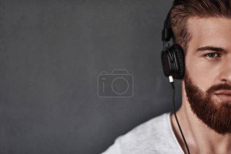 Photo pour Bel homme barbu écoutant de la musique dans les écouteurs en arrière-plan gris en studio - image libre de droit