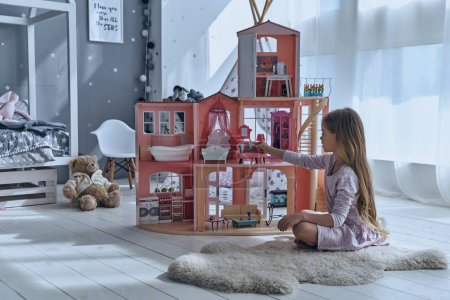 Photo for Adorable little girl playing with dollhouse in bedroom - Royalty Free Image
