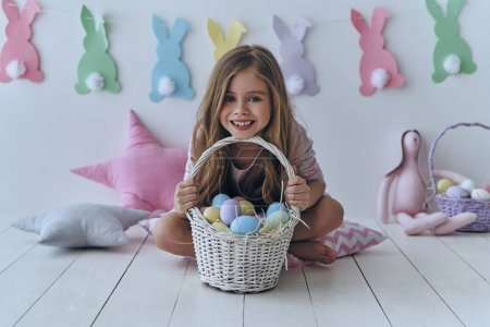 Photo for Adorable girl holding Easter basket and sitting on floor in studio, colorful decoration bunnies on background wall - Royalty Free Image