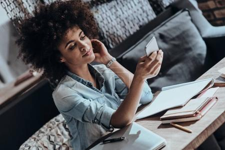Photo pour Belle femme africaine tape message sur téléphone intelligent - image libre de droit