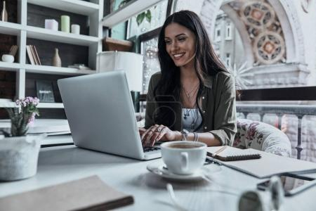 Photo for Attractive happy woman using laptop while sitting in restaurant - Royalty Free Image