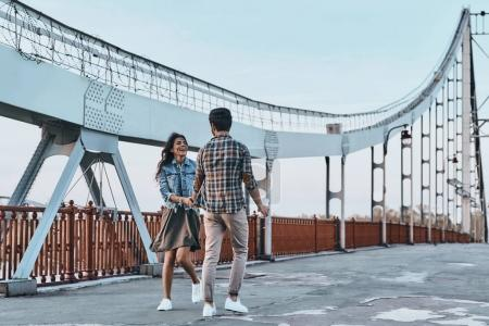 couple holding hands and walking on bridge
