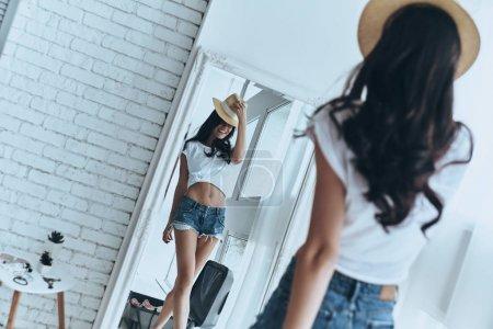 Photo pour Belle femme brune en chapeau posant et en regardant dans le miroir - image libre de droit