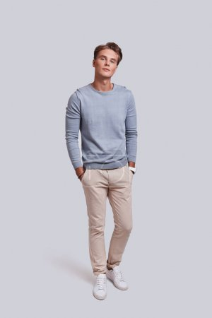Photo for Serious handsome young man in casual wear holding hands in pockets and looking at camera - Royalty Free Image