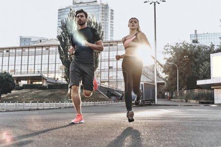 Photo pour Pleine longueur de couple sportif courant dans la ville près des bâtiments - image libre de droit