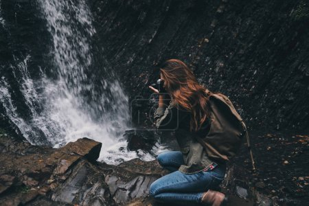 woman photographing waterfall in mountains