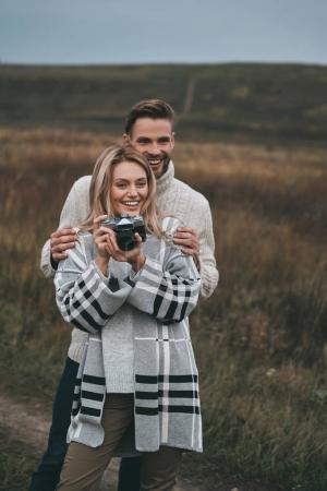 Photo pour Femme photographe avec caméra, homme embrassant sa petite amie dans le champ - image libre de droit