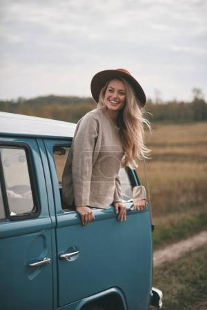 beautiful blonde woman leaning out the mini van window