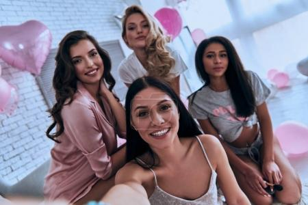 Self portrait of four attractive young women in pa...