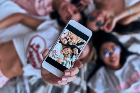 top view of four playful young smiling women in eyewear taking selfie with smart phone while lying on the bed