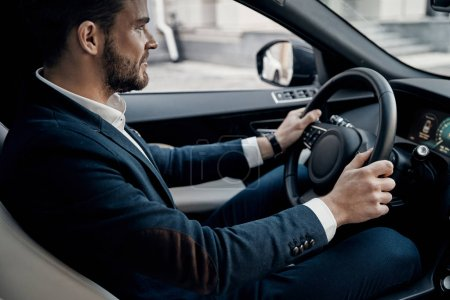 Handsome young man in suit driving a car