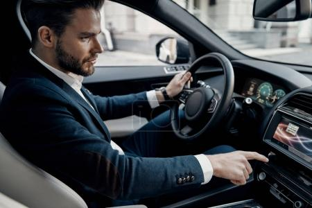 Handsome young man in suit pushing buttons while driving a car
