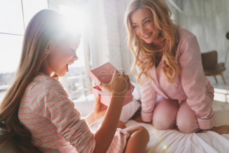Cute little girl opening birthday gift box while sitting with her mother on bed at home