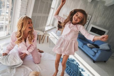 Going crazy together, Top view of cute little girl jumping on bed with mother at home