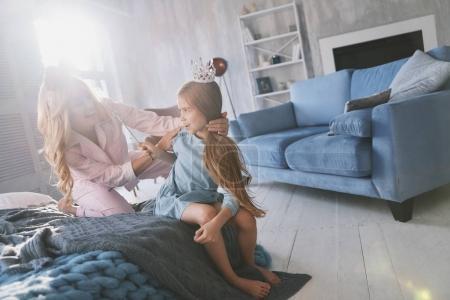 Piękna młoda matka, grając z Córka, siedząc na łóżku w domu