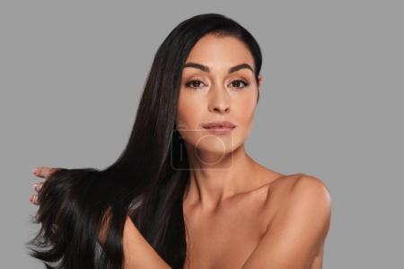 Photo pour Magnifique femme brune aux cheveux longs regardant la caméra et debout sur fond gris - image libre de droit