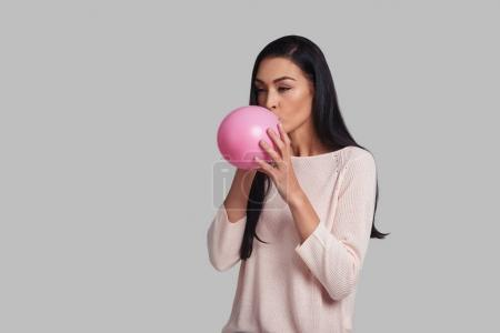 Studio shot of attractive young woman blowing up a pink party balloon