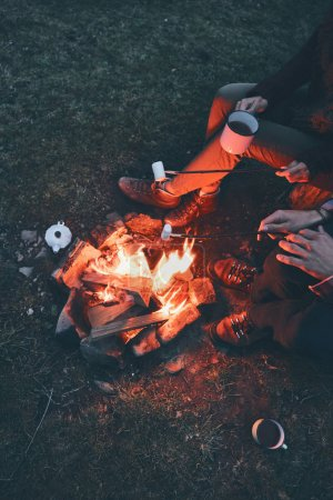 top view of couple roasting marshmallows over a campfire