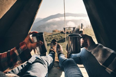 partial view, close up of couple enjoying view of mountain range while lying in tent with hot drinks in mugs