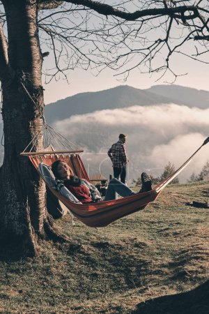 woman lying in hammock while her boyfriend enjoying beauty in nature, autumn camping in mountains