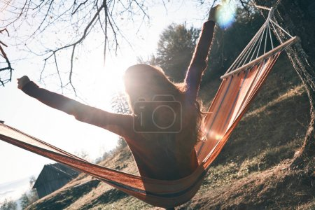 back view of woman relaxing in hammock and enjoying autumn in mountains