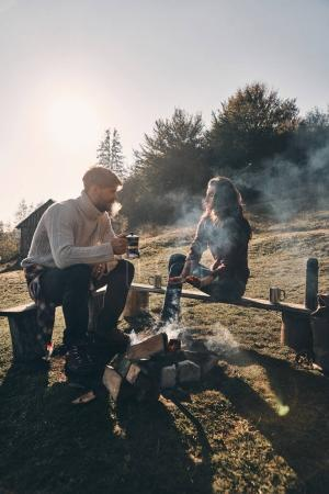 couple in love having hot drinks while spending carefree time in mountains near bonfire