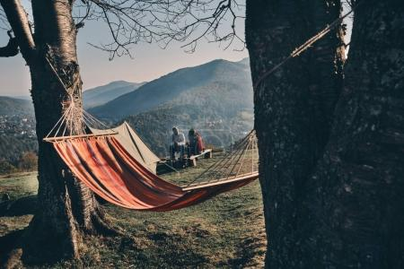 autumn camping in mountains, hanging hammock on trees, couple sitting on background
