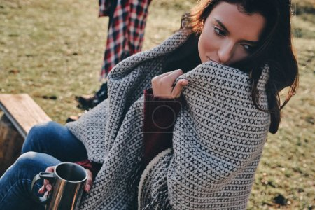Beautiful young woman covered with blanket and holding