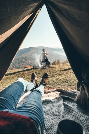Photo for Partial view, close up of woman enjoying view of mountain range and her boyfriend while lying in tent - Royalty Free Image