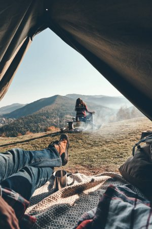 partial view, close up of man enjoying view of mountain range and his girlfriend while lying in tent