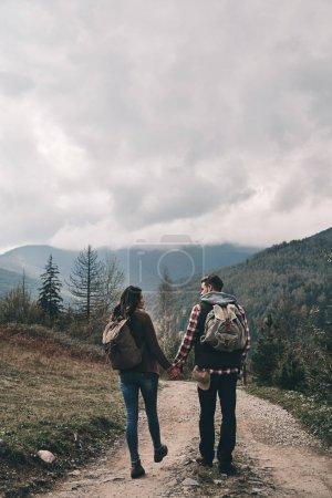 Vue arrière du couple avec des sacs à dos de marche sur route dans les montagnes de destinations voyage