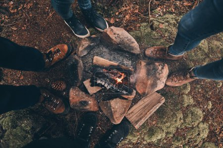 Photo for Partial view of people standing around campfire in forest - Royalty Free Image