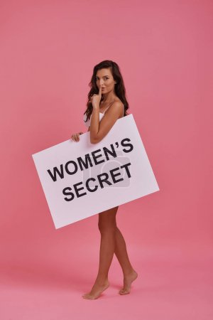 gorgeous young woman holding poster and gesturing gesturing quite with finger at mouth, banner with text: women secret