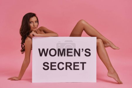 Beautiful young woman covered with poster while lying against pink background, text on banner: women secret