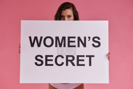 Young woman covering half of face with poster and looking at camera while standing against pink background, text on banner: women secret