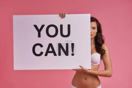 Attractive young woman covering half face with poster and looking at camera while standing against pink background, text on banner: you can