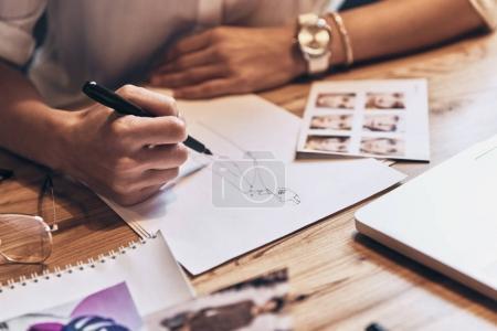 Photo pour Gros plan des croquis de dessin de femme assis à la table en bois avec ordinateur portable - image libre de droit