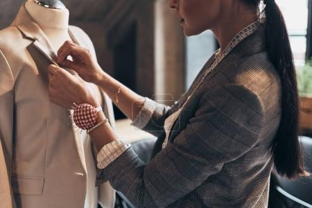 Photo pour Gros plan de couture femme tailleur avec veste de mode aiguille sur mannequin - image libre de droit