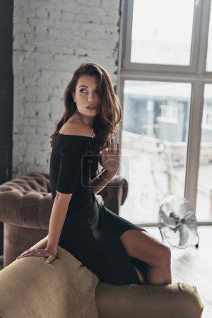 Photo pour La mode femme brune en robe élégante noire posant à la maison - image libre de droit