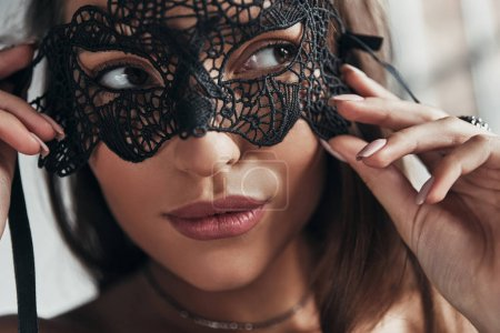 close up portrait of gorgeous woman wearing black carnival mask on eyes