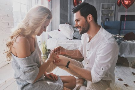 beautiful blonde young woman looking at engagement ring with smile while her boyfriend proposing her to marry