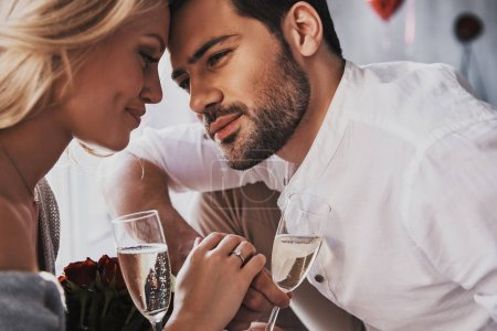 romantic young couple in love with champagne glasses celebrating valentines day
