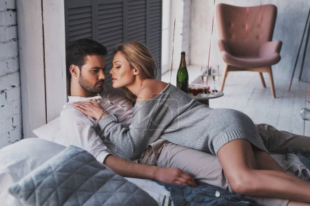 Caucasian ethnicity couple in love embracing while lying on bed at home