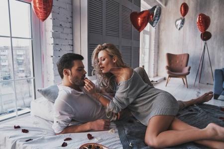 Photo pour Tu devrais essayer. Beau jeune couple mangeant des bonbons au chocolat et buvant du champagne tout en étant allongé sur le lit à la maison - image libre de droit