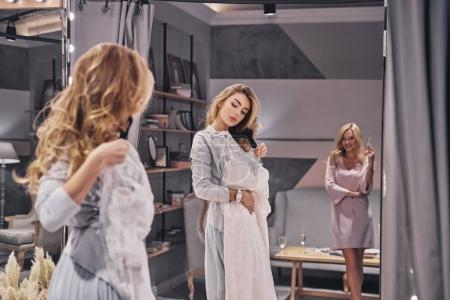 Photo for Attractive blonde woman choosing wedding dress in fitting room with bridesmaid - Royalty Free Image