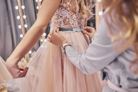 Close up of young woman measuring her girlfriends waist while standing in fitting room