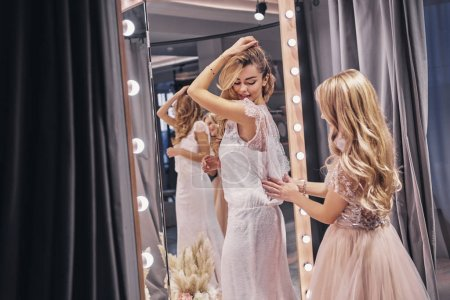 Photo for Young beautiful woman adjusting a dress on her girlfriend while standing in fitting room - Royalty Free Image
