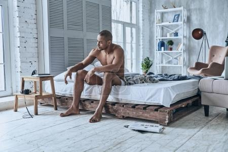 shirtless sleepy young African man sitting on bed at home