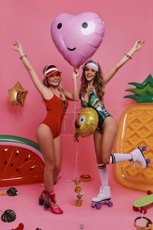Playful girls in swimwear holding balloons and looking at camera with smile while standing against pink background